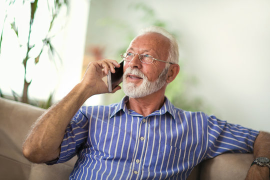 Senior man chatting on a mobile phone while relaxing on a sofa in his living room
