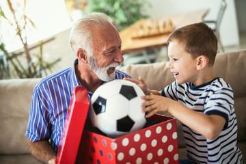Handsome senior grandfather presenting gift to happy grandson