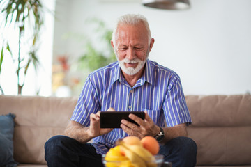 Senior man sitting on sofa and using digital tablet in living room