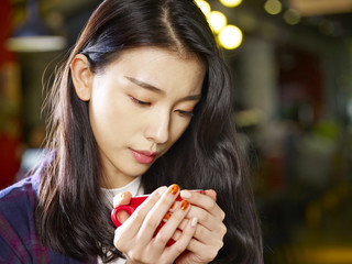 young asian woman holding a cup of coffee