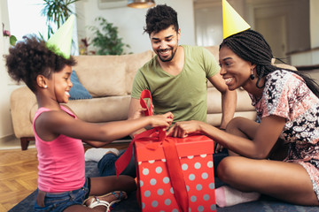 Happy black family at home. African american father, mother and child celebrating birthday, having fun at party. Young woman giving gift to daughter