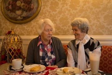 Senior friends interacting witch each other while having