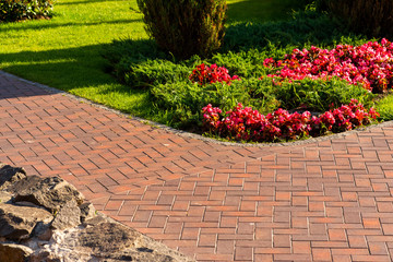 Foto op Canvas Zalm Path from red paving slab next to flowers in landscape design