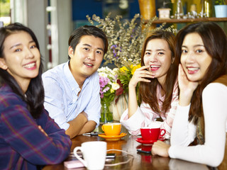 happy young asian adults looking at camera smiling in coffee shop