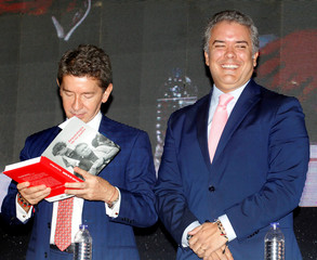 "Colombia's President-elect Ivan Duque reacts after giving a copy of his book ""Arqueologia de mi padre"" to the governor of Antioquia, Luis Perez, in Medellin, Antioquia"