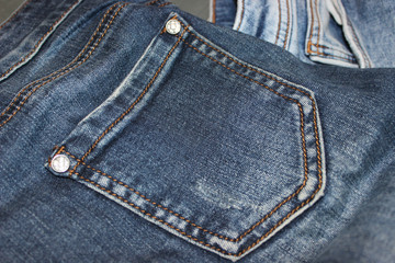 Details on denim pants, pocket and metal buttons, close-up. Free space for text