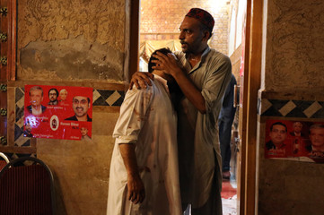 A political party worker comforts another after a suicide attack during an election campaign meeting in Peshawar