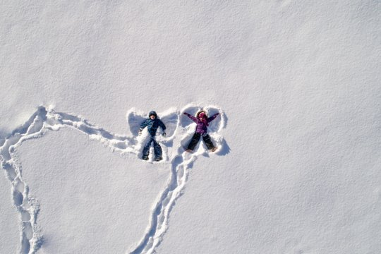 Top angle view of kids lying on snow and making snow angel shape