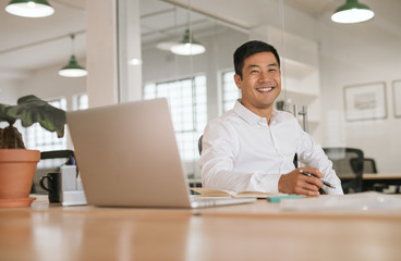 Smiling young Asian businessman working alone at his office desk