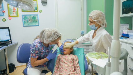 Child with a mother at a dentist's reception. The girl lies in the chair, behind her mother. The doctor works with an assistant. Procedure for drilling a tooth. Setting a temporary seal. Using the x