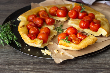 Homemade tart with cherry tomatoes of puff pastry with raw tomatoes and thyme on  dark wooden background. Tomatoes tart tatin. Rustic style.