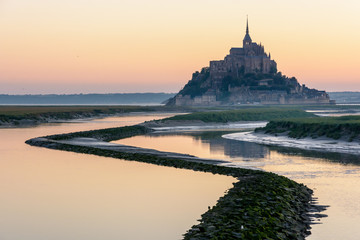 The silhouette of the famous Mont Saint-Michel tidal island in Normandy, France, seen at sunrise and high tide with the warm colors of the sky reflecting in the still waters of the Couesnon river.