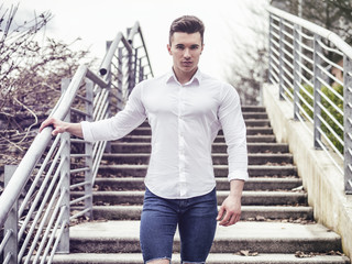 One handsome young man in urban setting in European city, standing, wearing white shirte and jeans