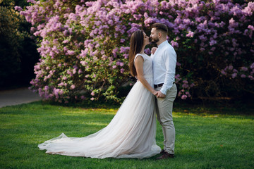 Sensual wedding couple of groom and bride in gorgeous dress hugging near the big purple flower bush in the green garden.