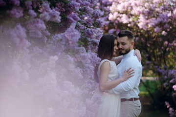 Side view of sensual couple of groom and bride in wedding dress hugging near the beautiful bush with purple flowers in the garden