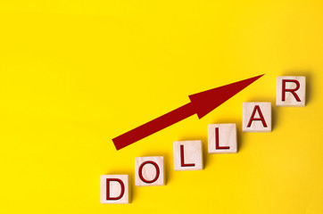 the growth of the dollar and the arrow going up. profit growth. concept of finance. exchange rate. wooden blocks on a yellow background