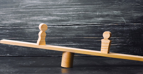 Figures of a man and a woman on the scales. inequality concept : man and women on a weighing balance, gender pay gap. divorce. Division of property in court. Social role in the family