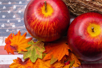 Large apples and autumn leaves with hay for harvest holiday USA theme