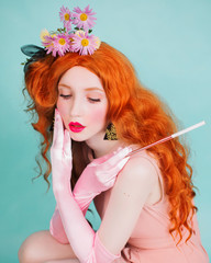Young perfect redhead girl with very long hair and pink gloves in studio on a blue background. Fabulous renaissance redhead model with flowers in red curly hair. Stylish perfect outfit