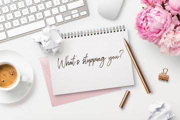 What's stopping you - business concept. Motivational quote written on a ring binder, feminine styled modern workspace with coffee, crumpled paper balls, a bunch of flowers and office gadgets, top view