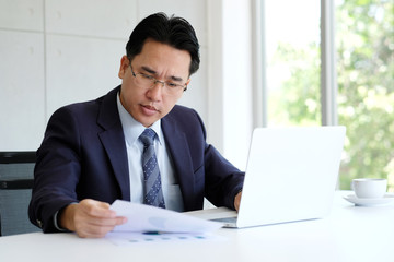 Asian businessman reading papers and working with laptop computer at office, business concept