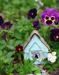 Small blue house in flowerbed with viola flowers. Lovely miniature house for greeting cards, wedding or birthday concept, real estate, downsizing, home ownership. Vintage summer background