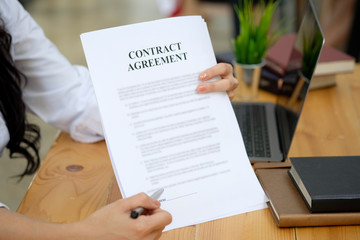 Businesswoman pointing sign terms and conditions document paper in board room.