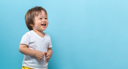 Toddler boy smiling on a bright blue background