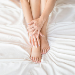 Female legs on bed. Cropped image of beautiful woman in bedroom. Horizontal photo, top view. Pedicure concept.