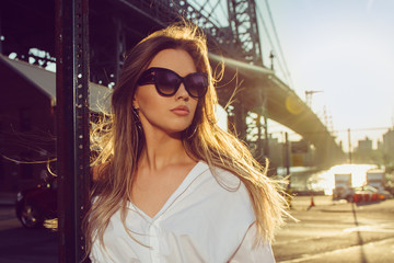 Elegant woman wearing sunglasses in the city at hot summer day