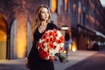 Beautiful girl hold and walk with rose flower bouquet after delivery in the city.