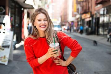 Beautiful smiling woman enjoy refreshment iced coffee drink on city street