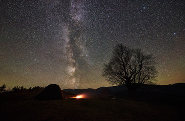 Campfire burning between two tourist tents, dark and lit from inside. Camping in mountain valley under beautiful night starry sky, Milky way. Big tree and distant mountain range on background