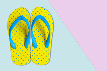Yellow sandals on pink and blue color background, flat lay photo