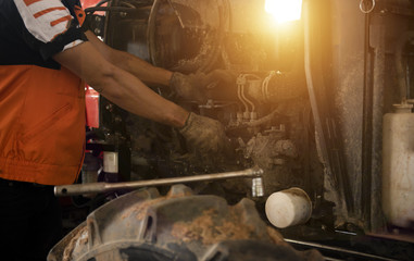 in asia Mechanic repairing Tractor engine old