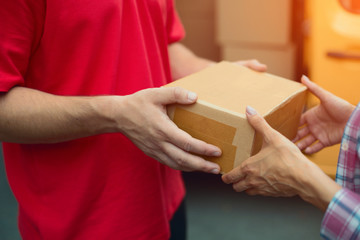 Close up shot of delivery man handing tan package box. Delivery man wearing red uniform handing cardboard delivery to customer.