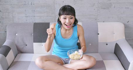 Woman watching the football match with snack