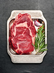 Fototapete - Raw steak ribeye with rosemary and garlic in metal tray, top view