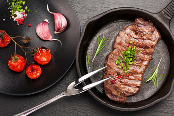 Wall Mural - grilled beef steak in cast-iron frying pan with baked vegetables
