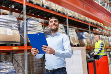 logistic business, shipment and people concept concept - happy businessman with clipboard at warehouse