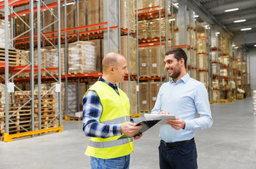 wholesale, logistic business and people concept - warehouse worker and businessman with clipboard and tablet pc computer talking