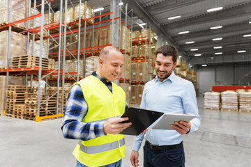 wholesale, logistic business and people concept - warehouse worker and businessman with clipboard and tablet pc computer