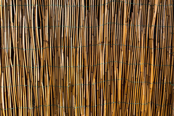 Beautiful wallpaper image of a fence made of bamboo sticks. Recycling materials from nature. No people.