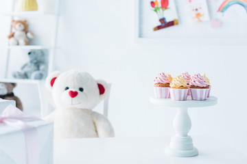 teddy bear sitting at table with cupcakes on stand