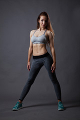 Sporty and sexy slim girl posing on grey background