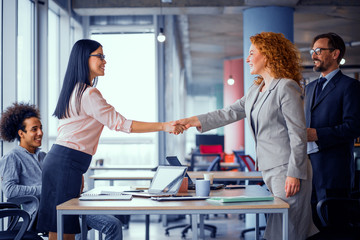 Working space. Two businesswomen shaking hands. Deal between two business teams. Toned concept.