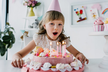 smiling kid in cone blowing out candles from birthday cake