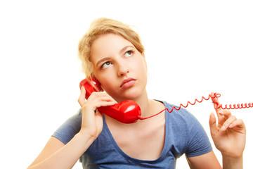 Frau hört frustiert Hintergrundmusik in Warteschleife
