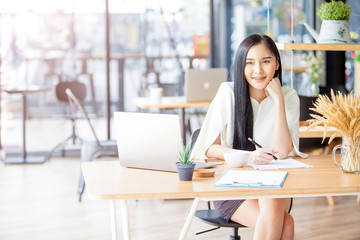 Protrait of Beautiful Asia businesswoman sitting at desk and working with laptop computer.