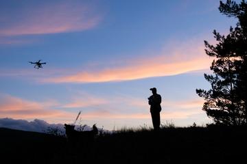 человек с собакой на закате запускают дрон